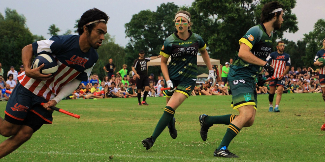 A chaser in an American jersey is shown holding a quaffle and running forward. One chaser in an Australian jersey is running toward them, while another Australian chaser is moving out of view of the camera. Two other American players, referees, and spectators are shown in the background.