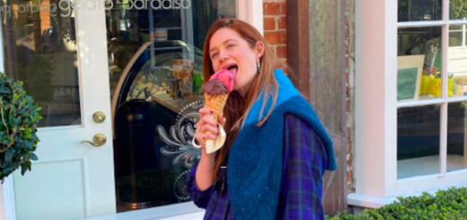 Bonnie Wright eats an ice cream cone while standing outside of a ice cream and gelato shop.