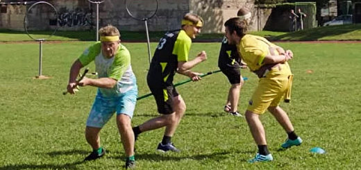 """Bradley Walsh is shown in a Slovenian jersey, holding his broom in his hands (being """"off broom""""). Barney Walsh is pictured beside him in an Aemona Argonauts jersey, standing in front of the snitch runner. Another Aemona Argonauts player and three hoops are visible in the background."""
