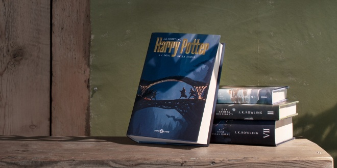 A stack of books is laid on a simplicistic table. The cover that is visible shows a stylized illustration of maybe the Three Brothers' tale against a magical blue background.