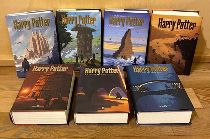 All Harry Potter books are laid out on a table with the new Italian covers that are stylish but evoke the colour and magic of the stories. They have iconic Harry Potter spaces and architecture in their focus.