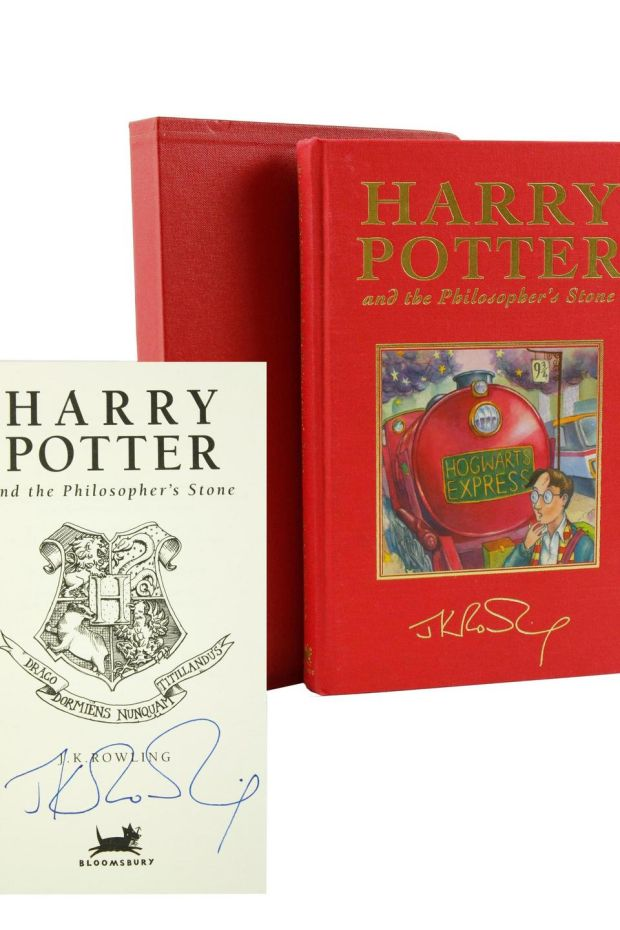 A bright red deluxe copy of Harry Potter and the Philosopher's Stone is pictured on a white backdrop, plus the title page signed by J. K. Rowling.