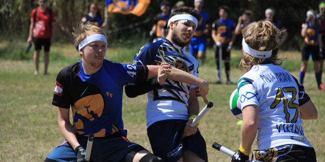 A chaser in a Vienna Vanguards jersey attempts to grab a chaser from the opposing team, while another chaser holding a quaffle looks on.