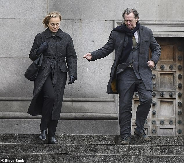 "Gary Oldman and Kristin Scott Thomas rush down a set of stairs during filming for ""Slow Horses."""