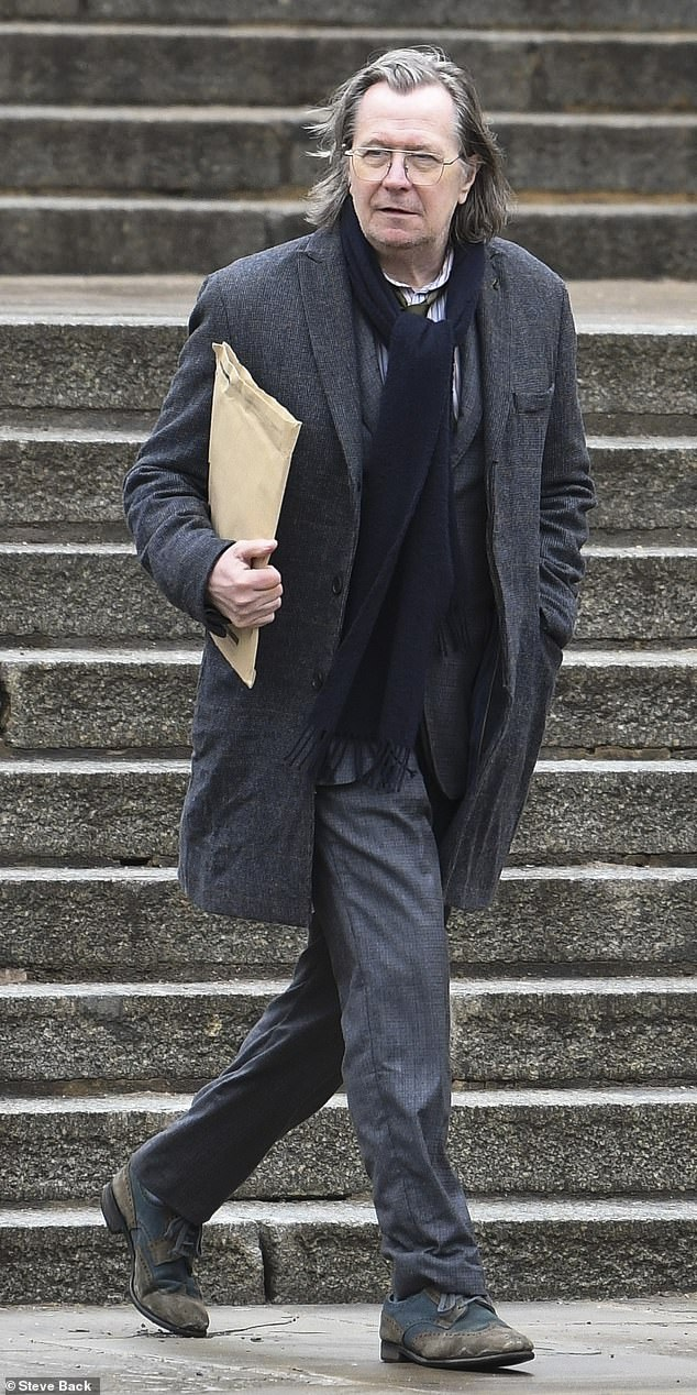 """Gary Oldman carries a folder that possibly contains important spy stuff during filming for """"Slow Horses."""""""