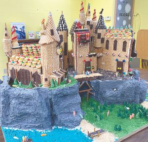 Father and son construct graham cracker castle for New Baden, Illinois, library display