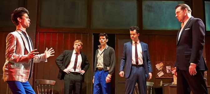 Five actors including Rupert Grint are standing on stage. Ben Whishaw is in a funny position, like he is mocking Brendan Coyle's character. They are all in suits.