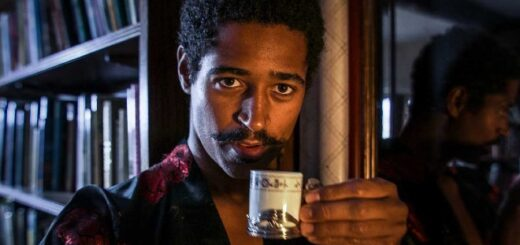Alfred Enoch is looking directly at the camera while sipping coffee from a fancy cup. He is in character as Lord Henry Wotton and is therefore also sporting a pointy moustache and a luxurious dressing robe.