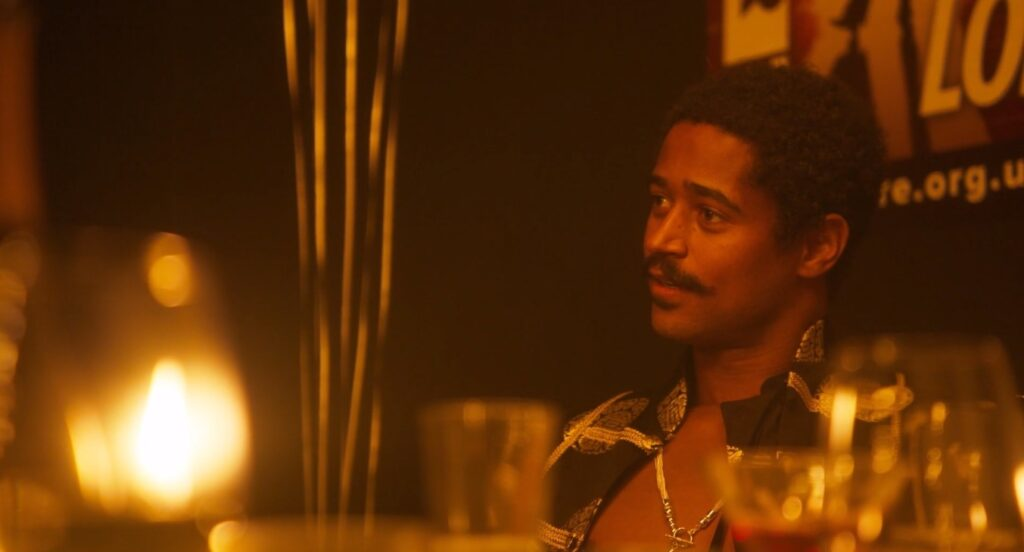 Alfred Enoch as Harry Wotton in The Picture of Dorian Gray is sitting by the wall at a dimly lit birthday party in a theater dressing room. He is wearing his shirt unbuttoned and he is staring at someone longingly.