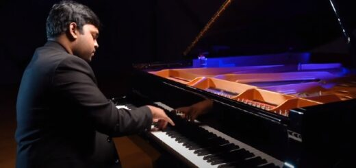 Eshan Denipitiya is sitting at a colorfully lit grand piano, playing.