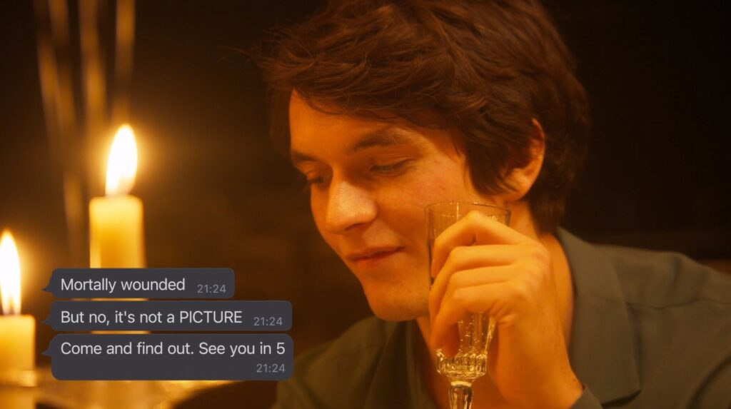 """We can see a close up of Fionn Whitehead as Dorian Gray sipping champagne while reading the following texts from Basil: """"Mortally wounded. But no, it's not a PICUTRE."""
