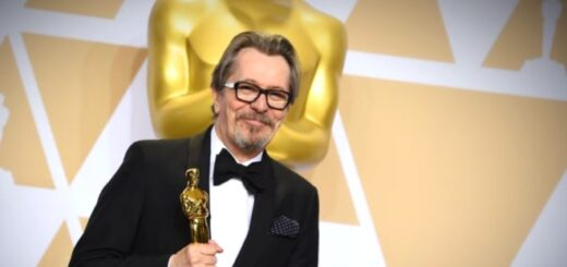 Gary Oldman is standing on the 2018 red carpet with his Oscar, very smily and proud.