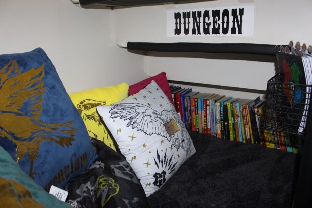 The underside of the stairs shows a dungeon sign in a Harry Potter themed cupboard. There are cushions and books in this reading nook.