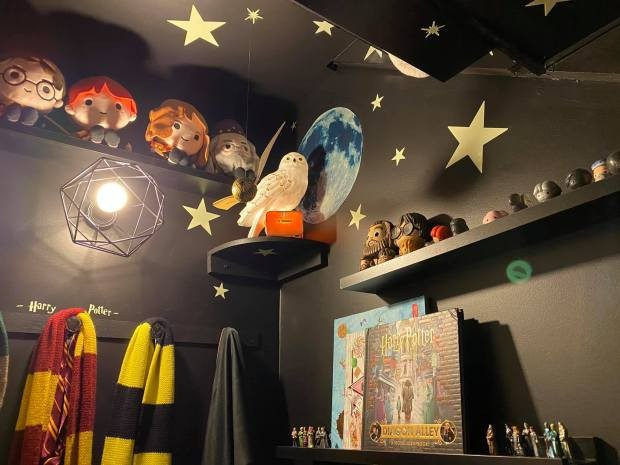 A cupboard under the stairs is pictured, painted with magical stars and stuffed with Harry Potter toys, stuffed owls, scarves, and pictures.