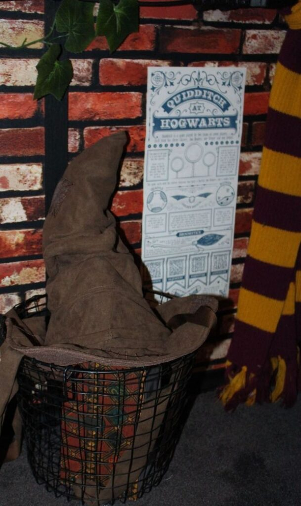 A Sorting Hat is placed in a tiny cupboard under the stairs that has lots of Harry Potter items.