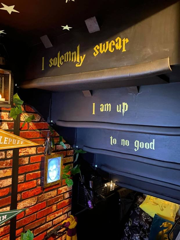 "In a cupboard, the underside of the staircase is painted with the quote ""I solemnly swear I am up to no good."" Under this, a cosy Harry Potter themed reading nook is found with cushions and books."