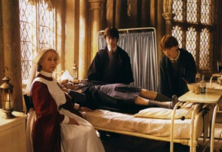 Hermione petrified in the hospital wing. Madam Pomfrey, Harry, and Ron are around her bed