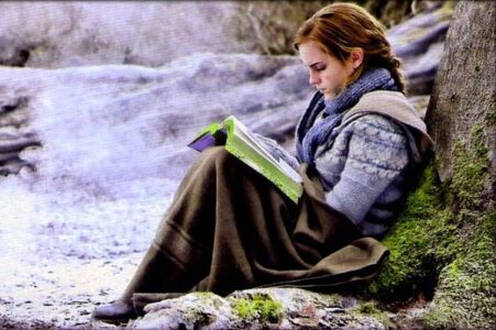 Hermione reading a book, sittingunder a tree