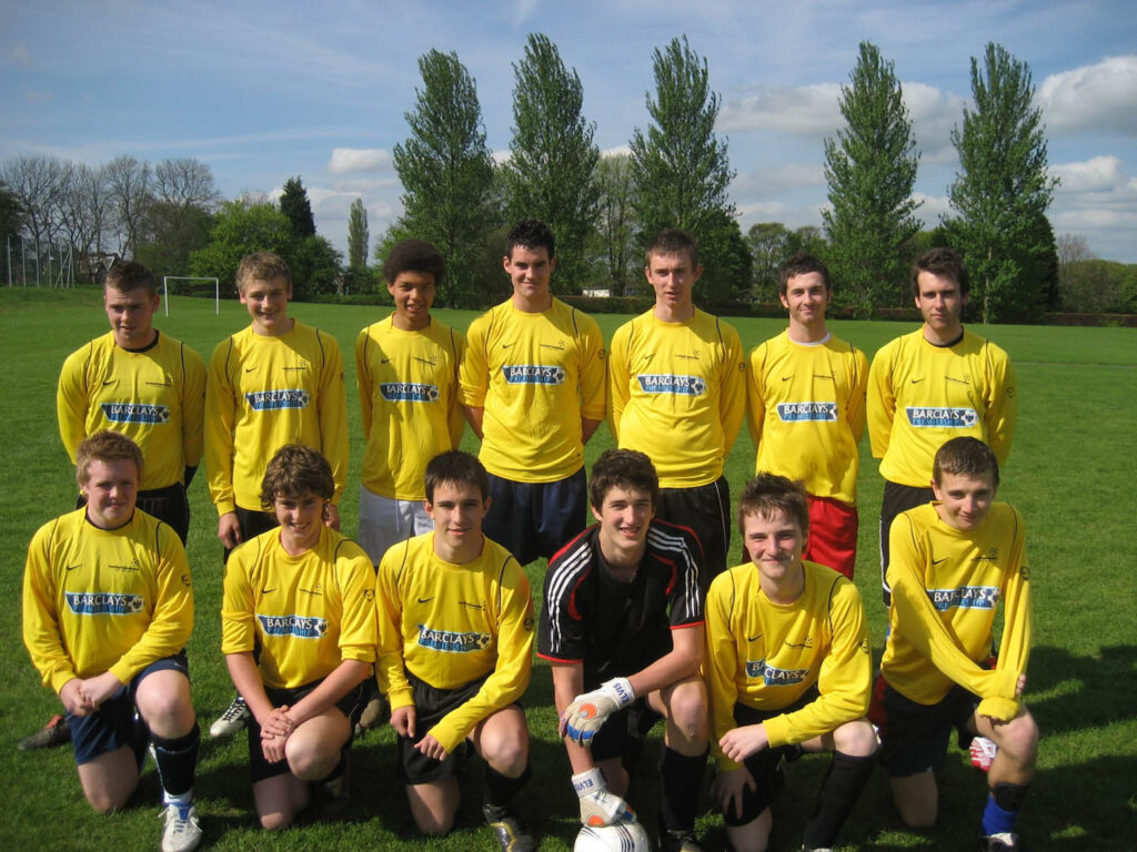 A school football team of teenage boys are posing for a group photo, including Matthew Lewis dressed in the yellow uniform in the back.