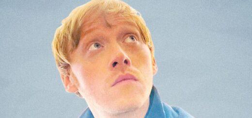 A portrait of Rupert Grint looking up, against a pale blue backdrop.