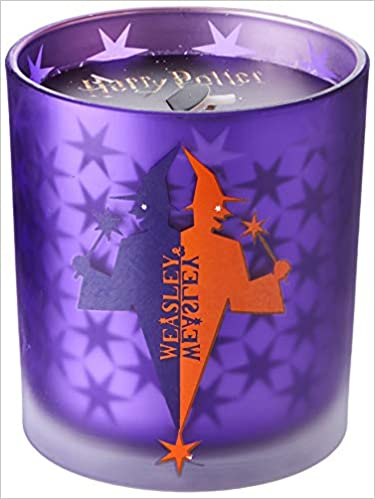 The Weasleys' Wizard Wheezes Glass Candle from Insight Editions is shown as pictured on Amazon. It has a purple and orange holder featuring the Weasleys' Wizard Wheezes logo from the films.