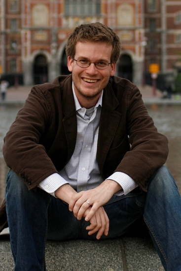 John Green wearing a plaid shirt, brown jacket and blue jeans.