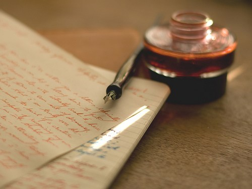 quill and ink bottle laying on top of parchment paper