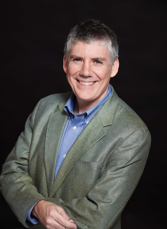 Rick Riordan wearing a green blazer and blue shirt