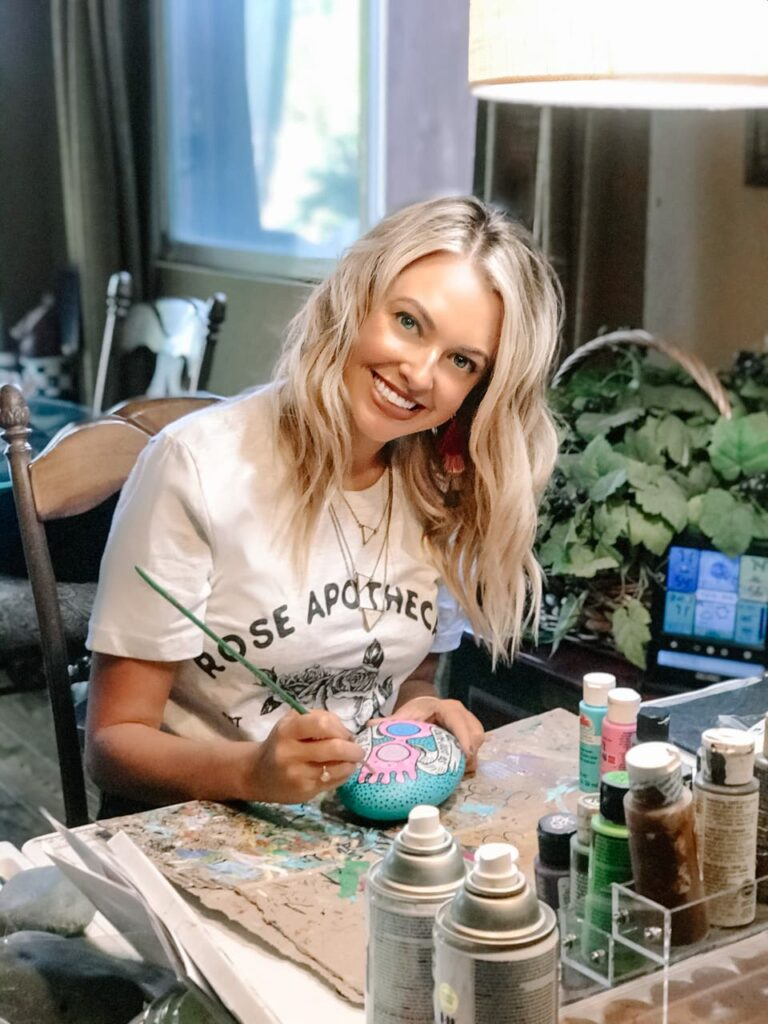 Kristen Newman, 30, blonde, is at her desk, painting a rock with Luna Lovegood's pink goggles while she is smiling at the camera.