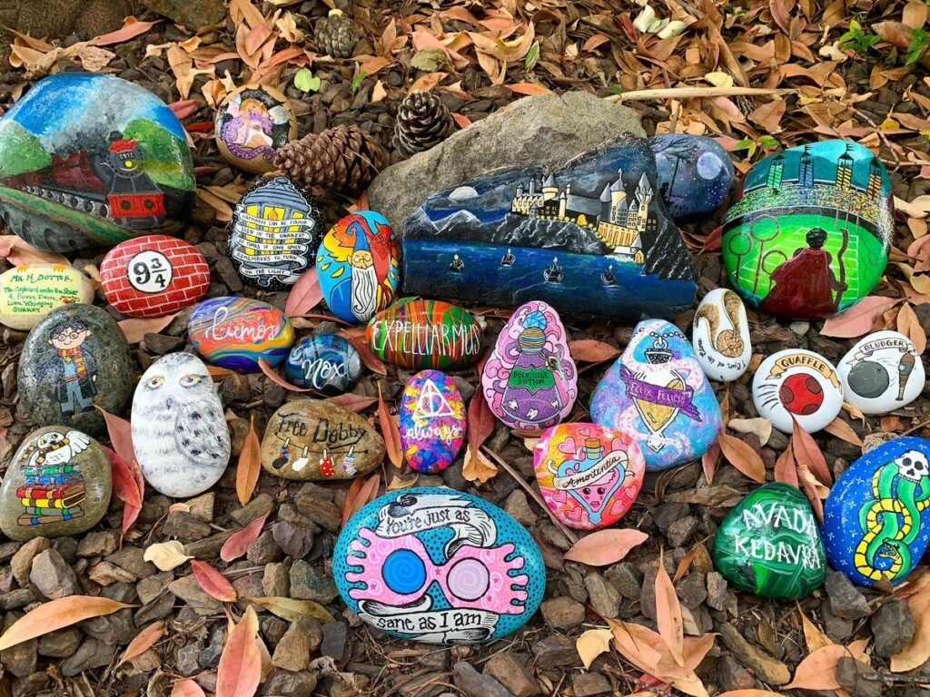 An assortment of painted rocks are arranged on a garden patch. They are painted with Harry Potter thins like Hedwig, Luna's goggles, Hogwarts at night, Harry hovering over a Quidditch pitch on a broomstick, spells, the Platform 9 and 3/4 sign, etc.