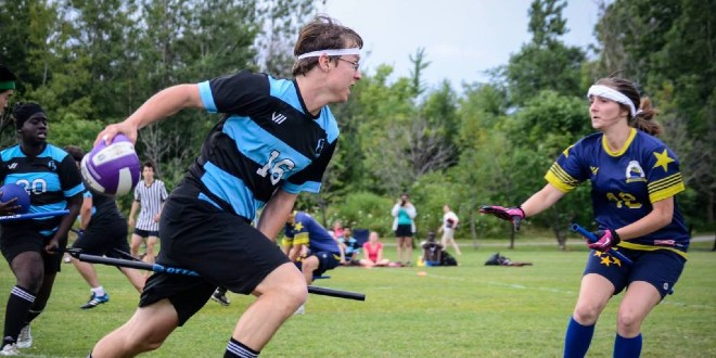 A chaser from the Ottawa Black Bears runs forward from the left while holding a quaffle. A chaser from the Washington Admirals is shown at the right, while a beater from the Ottawa Black Bears is shown in the background at the left.