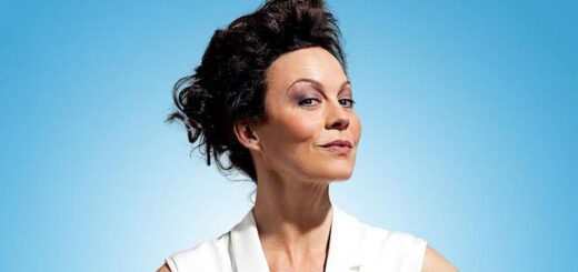 A picture of Helen McCrory. She is wearing a white outfit against a blue background and is facing the camera.