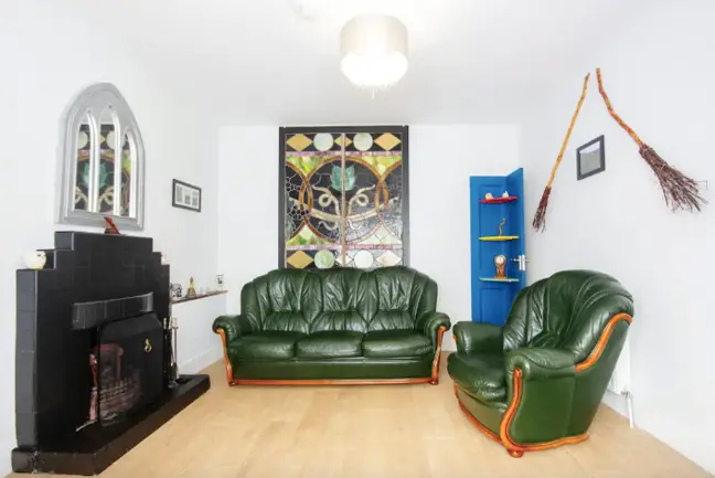 The Irish Draiocht Magic House's living area is decorated with broomsticks on the walls and Slytherin-colored furniture.