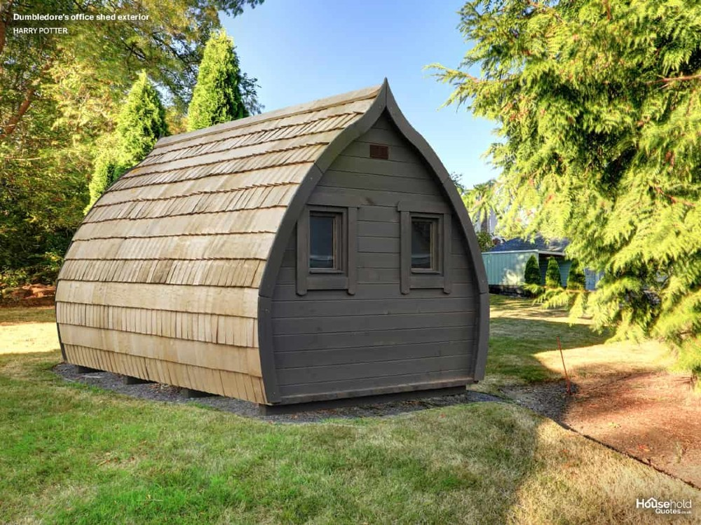 In a sunny garden, there is a designer shed pictured, with an upside-down drop shape. It is made of wood and looks like a fairy-tale cabin.