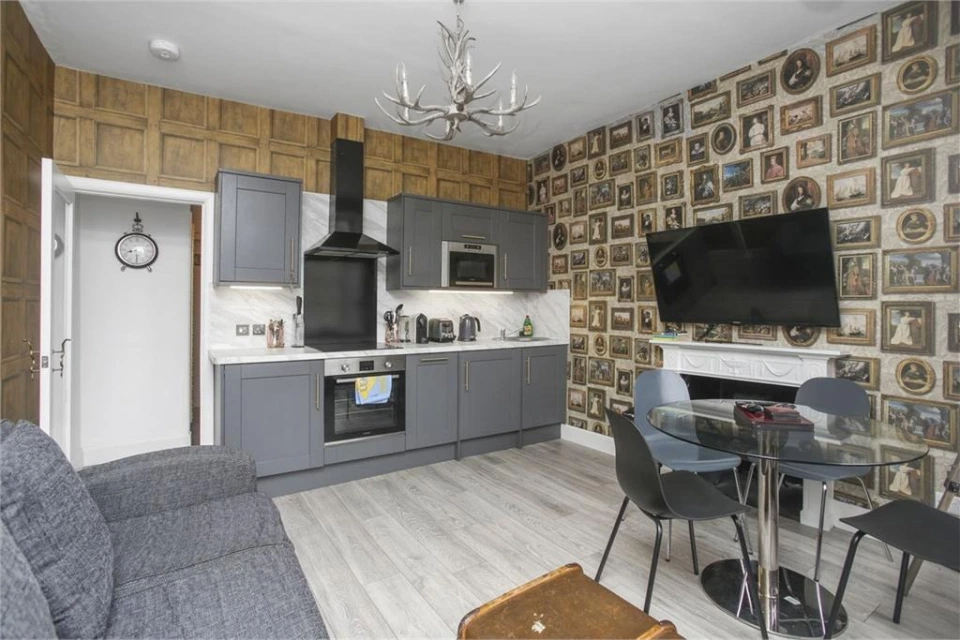 """""""Potter"""" Airbnb in Edinburgh mixes modern and magical with its updated kitchen and portrait wallpaper."""