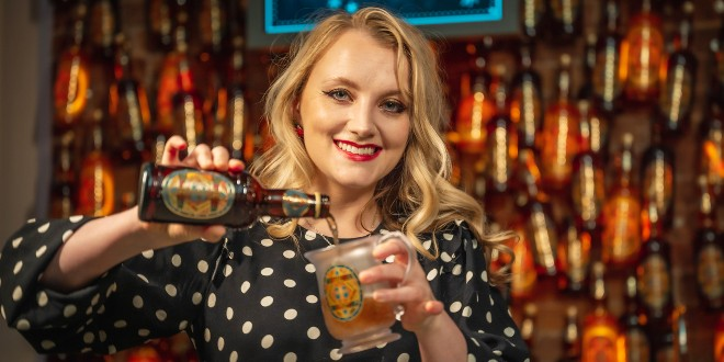 Evanna Lynch is pouring Butterbeer from a bottle into a glass with HP labels with a backdrop of a Butterbeer bar with floating bottles overhead.