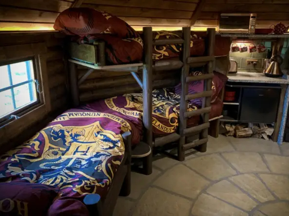The Hagridd's Hideaway interior resembles the cozy Gryffindor dormitory with maroon Hogwarts crest bedding.