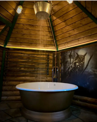 The Hagridd's Hideaway in England has a bathroom with a bowl tub and waterfall shower.
