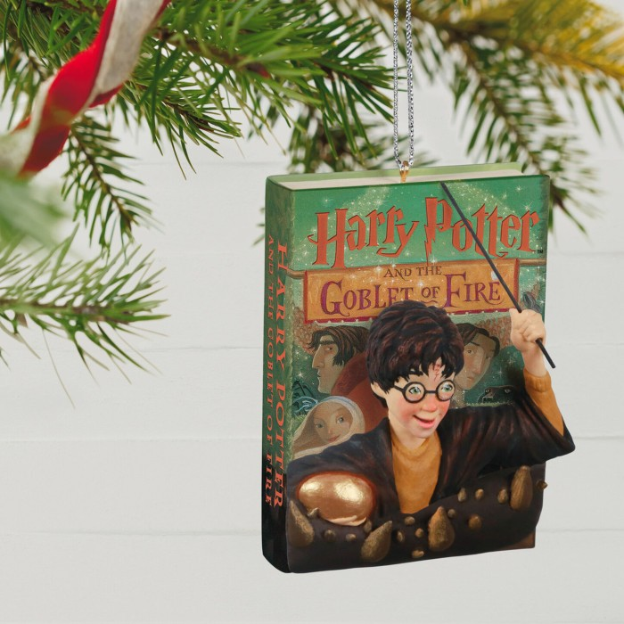 A three-dimensional Christmas ornament of Harry Potter and the Goblet of Fire is hanging from a Christmas tree branch.