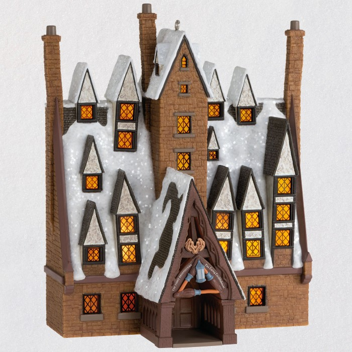A minuature ornament of a snowy Three Broomsticks inn is pictured against a white backdrop, with lots of rooftop windows that light up when the ornament is connected to a light source.