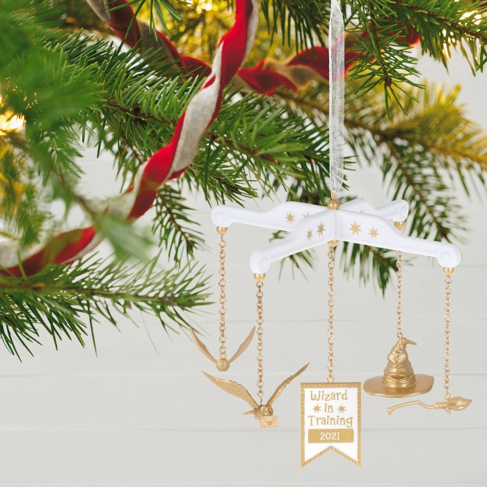 """A tiny baby mobile ornament in white and gold is hanging from a Christmas tree branch. A golden snitch, an own, aa sorting hat and a broomstick, as well as a sign saying """"Wizard in training 2021"""" are hanging from the ornament."""