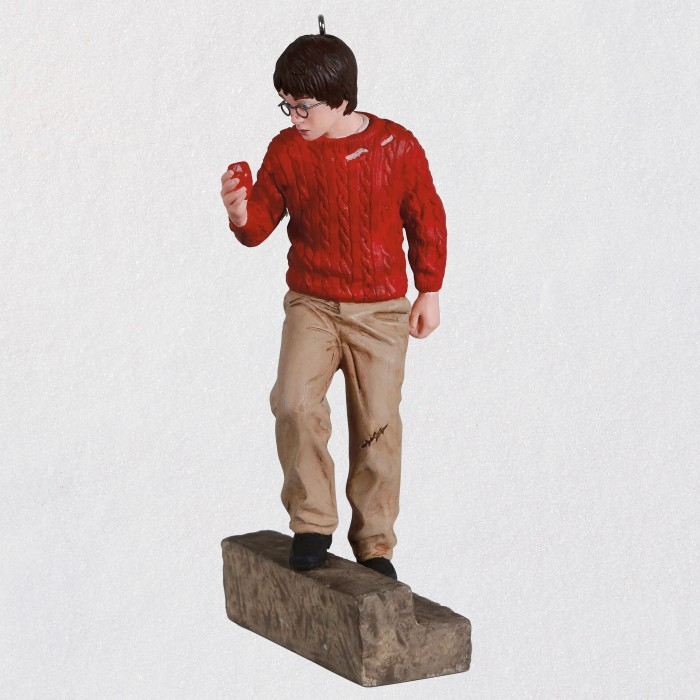 Against a white backdrop, a lifelike ornament of 11-year old Harry is pictured as he is holding the Sorcerer's Stone, in the red sweater and brown pants as seen in the movie.