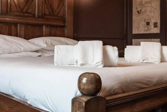 A comfortable hotel bed is pictured in a cozy but stylish hotel room with wooden paneling and Marauders Map wallpaper.