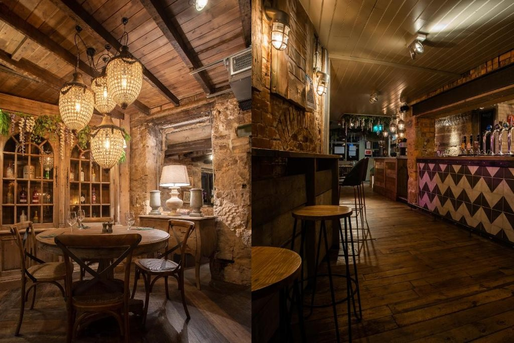 Left: a cosy restaurant table with lovely chandelier lights and bright lamps is pictured. The walls are made of stone, it has a medieval inn vibe. Right: the same restaurant from another angle, with a long bar and bar stools by the wall. It's dark but warm.