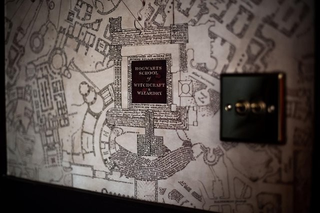 A hotel room wall can be seen from up close with the Marauders' Map as wallpaper.