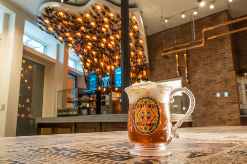 A perfect pour of foamy Butterbeer is placed on a table in the front with a backdrop of a cool bar with Butterbeer bottle lanterns above the counter.