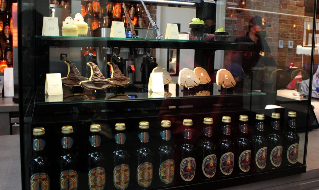 There is a bar with fun cookies on display in the shape of sweaters and Sorting Hats, with a row of bottled butterbeers in the front.
