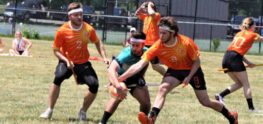 Eight quidditch players in orange jerseys are pictured, and one of the chasers is trying to take the quaffle from another chaser in a cyan jersey.