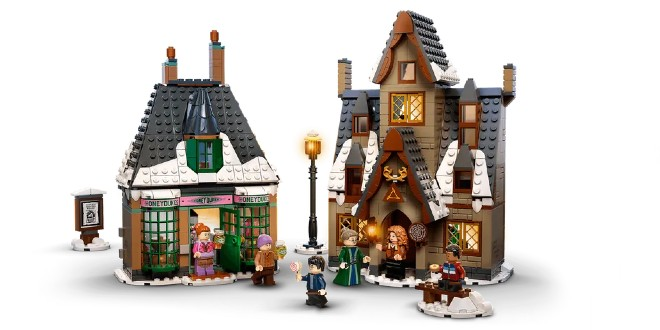 Against a white backgrop, there are two fabulous LEGO buildings fromt he shopfront side. On the left is Honeydukes Sweetshop and on the right is the Three Broomsticks inn. There are some characters from Harry Potter millin around, a streetlamp, a bench, and a wanted poster of Sirius Black.