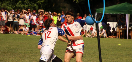 A beater from the United States tries to tackle a beater from Team UK who is holding a blue bludger. There is a hoop next to them.